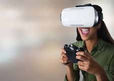 mujer que juega con el regulador del juego de ordenador y las auriculares de la realidad virtual con backgrou borroso brillante Foto de archivo