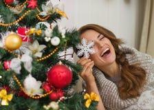 Mujer que juega con la decoración del árbol de navidad Imagenes de archivo