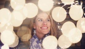 Mujer que juega con las luces de hadas en el invierno al aire libre foto de archivo