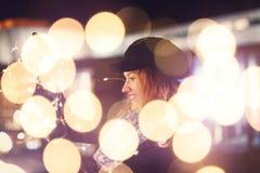 Mujer que juega con las luces de hadas en el invierno al aire libre imagen de archivo libre de regalías