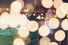 Mujer que juega con las luces de hadas en la mirada al aire libre del invierno lejos fotografía de archivo libre de regalías