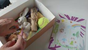 Mujer que juega con los juguetes de los ni?os de una caja almacen de metraje de vídeo