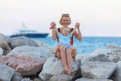 Mujer que juega con su bebé afuera El concepto de una vida familiar hecha y derecha feliz fotos de archivo