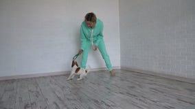 Mujer que juega con su perro en casa almacen de metraje de vídeo