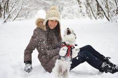 Mujer que juega con su perro en el bosque del invierno Foto de archivo libre de regalías