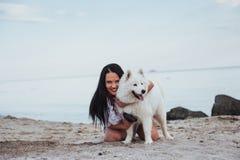 Mujer que juega con su perro en la playa Fotos de archivo libres de regalías