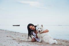 Mujer que juega con su perro en la playa Imágenes de archivo libres de regalías