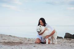 Mujer que juega con su perro en la playa Imagen de archivo libre de regalías
