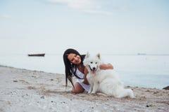 Mujer que juega con su perro en la playa Foto de archivo