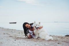 Mujer que juega con su perro en la playa Fotos de archivo