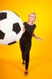 Mujer que juega con un balón de fútbol Imagen de archivo