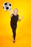 Mujer que juega con un balón de fútbol Fotos de archivo