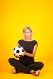 Mujer que juega con un balón de fútbol Imágenes de archivo libres de regalías