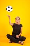 Mujer que juega con un balón de fútbol Foto de archivo libre de regalías
