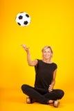 Mujer que juega con un balón de fútbol Fotos de archivo libres de regalías