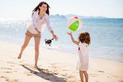 Mujer que juega con una pelota de playa Imagen de archivo libre de regalías