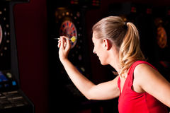 Mujer que juega dardos Imagenes de archivo