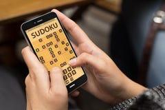 Mujer que juega el sudoku app Fotos de archivo libres de regalías