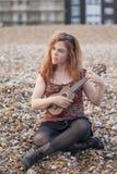Mujer que juega el ukulele imagen de archivo