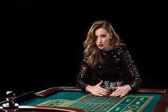 Mujer que juega en casino La mujer estaca pilas de microprocesadores que juegan rou Imagen de archivo libre de regalías
