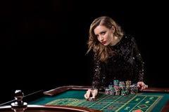 Mujer que juega en casino La mujer estaca pilas de microprocesadores que juegan rou Foto de archivo