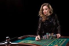 Mujer que juega en casino La mujer estaca pilas de microprocesadores que juegan rou Imagenes de archivo