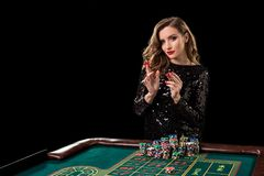 Mujer que juega en casino La mujer estaca pilas de microprocesadores que juegan rou Foto de archivo libre de regalías