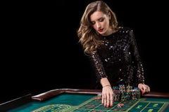 Mujer que juega en casino La mujer estaca pilas de microprocesadores que juegan rou Fotos de archivo