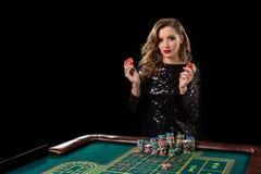 Mujer que juega en casino La mujer estaca pilas de microprocesadores que juegan rou Imágenes de archivo libres de regalías