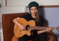 Mujer que juega en la guitarra Imagen de archivo libre de regalías