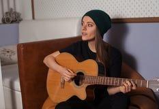 Mujer que juega en la guitarra Fotografía de archivo