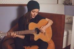 Mujer que juega en la guitarra Fotografía de archivo libre de regalías