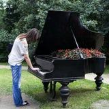 Mujer que juega en un piano viejo fotos de archivo