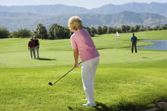 Mujer que juega a golf fotos de archivo