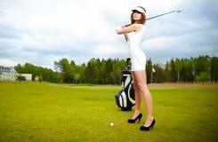 Mujer que juega a golf en un verde Foto de archivo libre de regalías