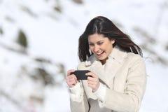 Mujer que juega a juegos en un teléfono elegante el vacaciones de invierno Fotos de archivo libres de regalías