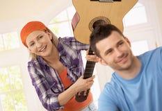 Mujer que juega la broma del ataque de la guitarra Imágenes de archivo libres de regalías