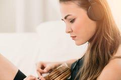 Mujer que juega la guitarra y la música que escucha foto de archivo libre de regalías