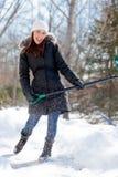 Mujer que juega mientras que traspala nieve Fotografía de archivo libre de regalías