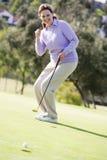 Mujer que juega a un juego del golf Foto de archivo libre de regalías