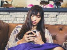 Mujer que juega un teléfono en el café imágenes de archivo libres de regalías
