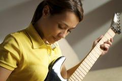 Mujer que juega y que entrena con la guitarra eléctrica en casa Imagen de archivo