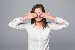 Mujer que la cubre ojos aislados en fondo gris Foto de archivo