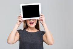 Mujer que la cubre ojos con la pantalla de tableta en blanco Imagenes de archivo
