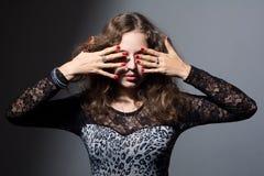 Mujer que la cubre ojos con sus manos en un fondo gris Fotos de archivo libres de regalías