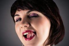 Mujer que lame atractivo los labios Fotos de archivo