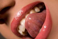 Mujer que lame los dientes con la lengüeta Fotos de archivo
