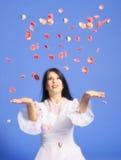 Mujer que lanza los pétalos color de rosa Fotografía de archivo libre de regalías
