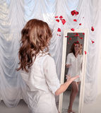 Mujer que lanza los pétalos color de rosa cerca del espejo fotos de archivo