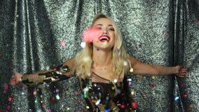 Mujer que lanza para arriba y que sopla en el confeti almacen de metraje de vídeo